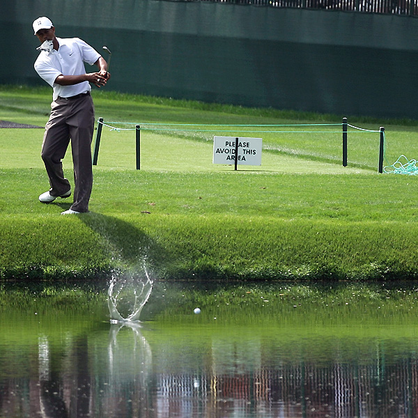 With a glove in his mouth, Tiger Woods shows there is more than one way to get over a water hazard.