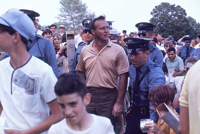 Arnold Palmer gets escorted past fans by police officers during the 1967 U.S. Open at Baltusrol Golf Club in Springfield, N.J.