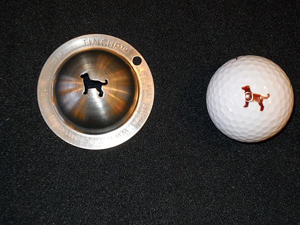 The quest for personalized style extends even to the golf ball, which players can now mark with the Tin Cup Personal Imprinting System, which uses die-cut tin cups, with cutouts of various favorite images — a dog (shown here), a dolphin, a bowtie, a ribbon, and so forth. You just place the cup over the ball and use a Sharpie to mark your design.