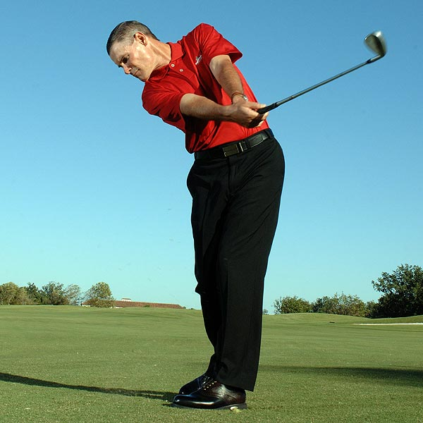 STEP 3                                          On your downswing, feel as though your whole left side is pulling the club down and into the back of the ball. Accelerate through the ball and dig up some turf. Since all you're trying to do is trap the ball, stop your finish when your hands reach about hip height.