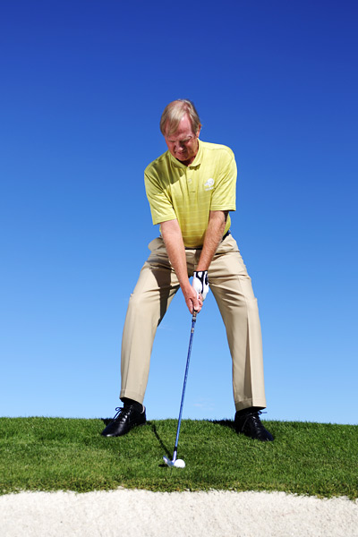 How to Keep Your Balance From Awkward Lies                      Stabilize your lower body so you can worry about hitting the green (not falling down!)                                           By Peter Krause                     Top 100 Teacher                                                               The Situation                                          Your approach has landed in a spot you didn't think possible: Hanging above a bunker on a severe downslope.                                          The Solution                                          Take a more stable stance and swing with your hands and arms to make easy work of this seemingly difficult lie.                                          Pretend you're riding a horse to add stability to your swing and to make sure you don't tumble into the bunker.