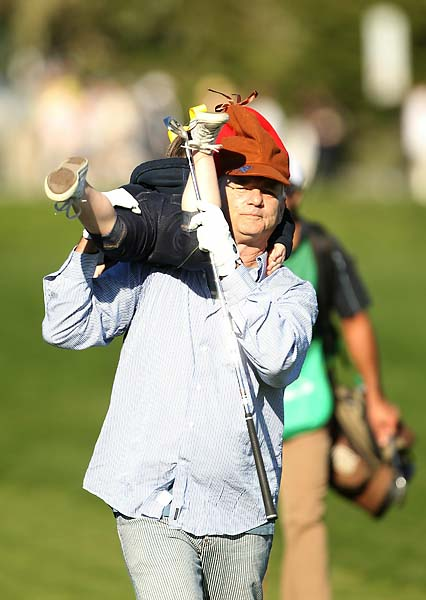 Bill Murray carries a girl that he picked from the crowd down the 17th fairway during the third round of the 2011 AT&T Pebble Beach National Pro-Am.