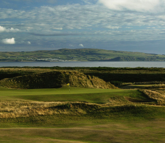 "Mark Calcavecchia: ""Royal Troon is my favorite links course because I won the Open there in 1989! I loved the course at first sight. Every hole just fit my eye.""                                              Pictured: A general view of the 'Postage Stamp,' par-3 8th green with the town of Ayr behind."