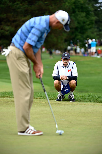 Caddie Fluff Cowan helps Jim Furyk line up a putt during the final round of the RBC Canadian Open at the Royal Montreal Golf Club
