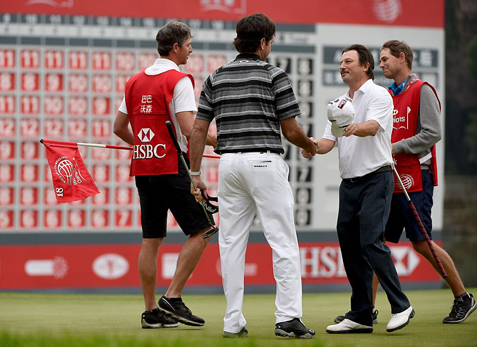 Bubba Watson is congratulated by Tim Clark of South Africa after his victory on the first playoff hole during the final round of the WGC-HSBC Champions in Shanghai Sunday.