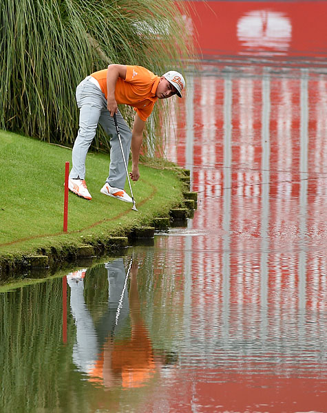 Rickie Fowler takes his ball from the water on the 18th hole during the final round of the WGC-HSBC Champions at the Sheshan International Golf Club. Fowler finished one shot out of the playoff.