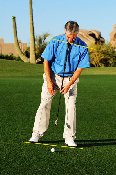 HOW TO KNOCK IT ON FROM A DOWNSLOPE                                                                     First, set your body, including your shoulders, parallel with the slope. Once you achieve that, do the same with your swing. Here's how:                                                                     Step 1: Take your address with the ball positioned an inch forward of where you play it with the club in your hand. To know for certain that you nailed your posture, line up your club with the buttons on your shirt. If the shaft points at the ball (not in front of it), you're solid.