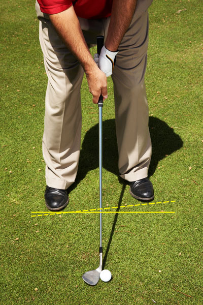 HOW TO LOFT THE BALL HIGH, SHORT AND SOFT                                          STEP 1: Address                     Take your address with the clubface slightly open and your feet aimed five yards left of your target. Position the ball just forward of center, choke down an inch and weaken your grip until the Vs formed by your forefingers and thumbs point a shade left of your shirt buttons.