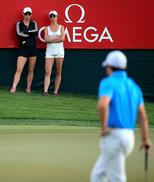 Rory McIlroy's fiancee Caroline Wozniacki and an unidentified friend watch McIlroy in the third round of the Dubai Desert Classic.