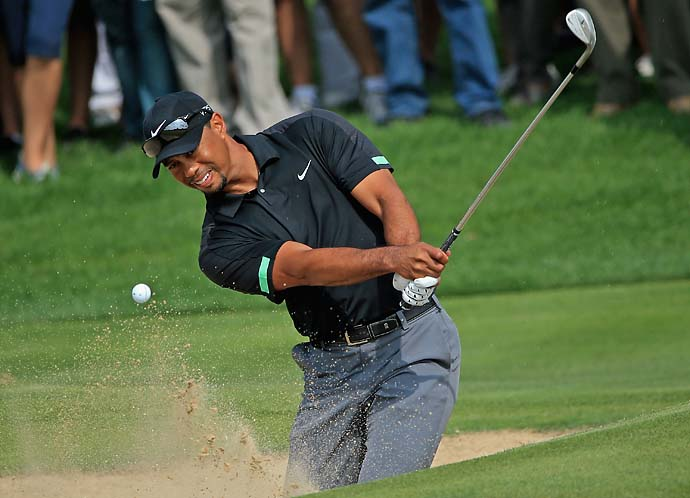 Tiger Woods plays a bunker shot on the third hole during the second round of the 2014 Omega Dubai Desert Classic.