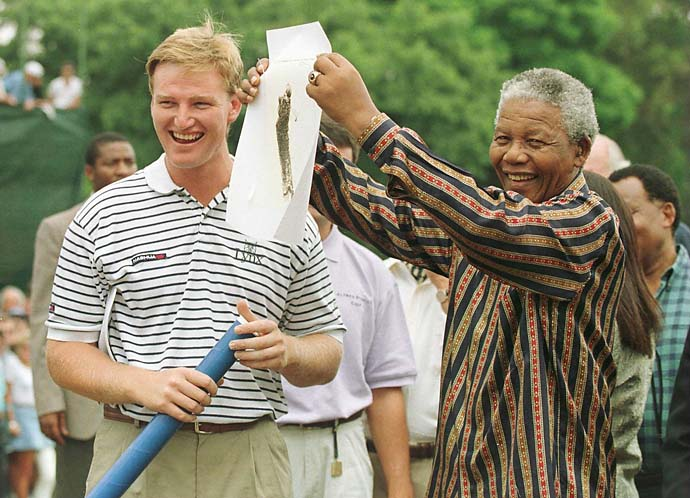 Ernie Els and President Nelson Mandela of South Africa share a laugh in February 196 as Mandela shows a sketching of Els to the crowd before the final round of the Alfred Dunhill South African PGA Championship at Houghton Golf Club, Johannesburg, South Africa.