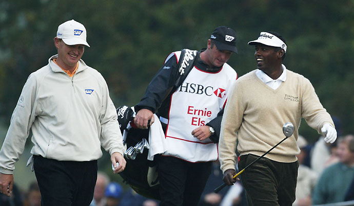 Vijay Singh smiles with Ernie Els on the 4th hole during the third day of the HSBC World Match Play Championship at Wentworth Golf Course on Oct. 18, 2003.