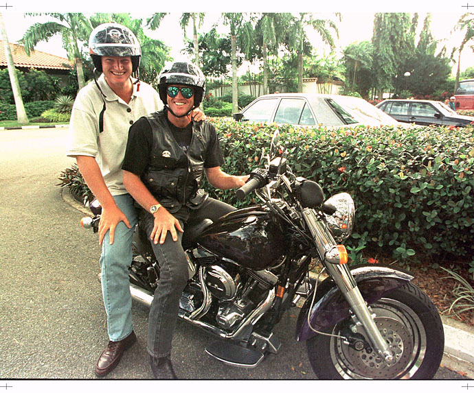Ernie Els and Greg Norman stop to pose atop a Harley Davidson motorcycle as they arrive at the course for the  final day of the Johnnie Walker Classic golf tournament, Jan. 28, 1996, in Singapore.