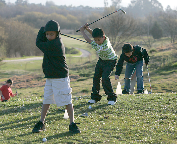 Jose (center) has developed into one of the better players at the The First Tee in Salinas. He gets help with his game from full-time paid instructors on staff.
