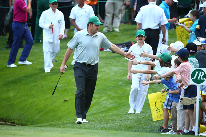 Three-time Masters champ Nick Faldo greets young fans.