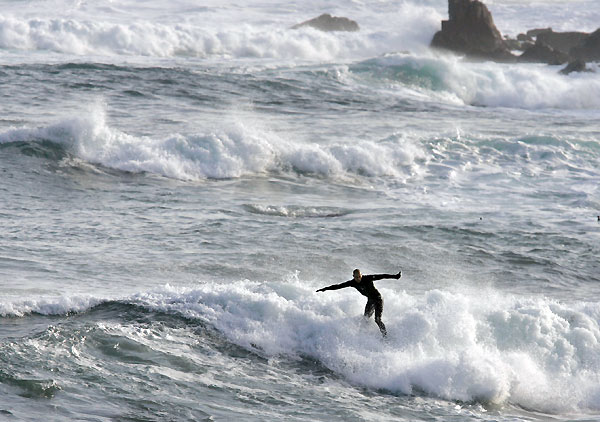 Surfer Kelly Slater caught some waves off No. 18 at Pebble Beach after finishing his round.