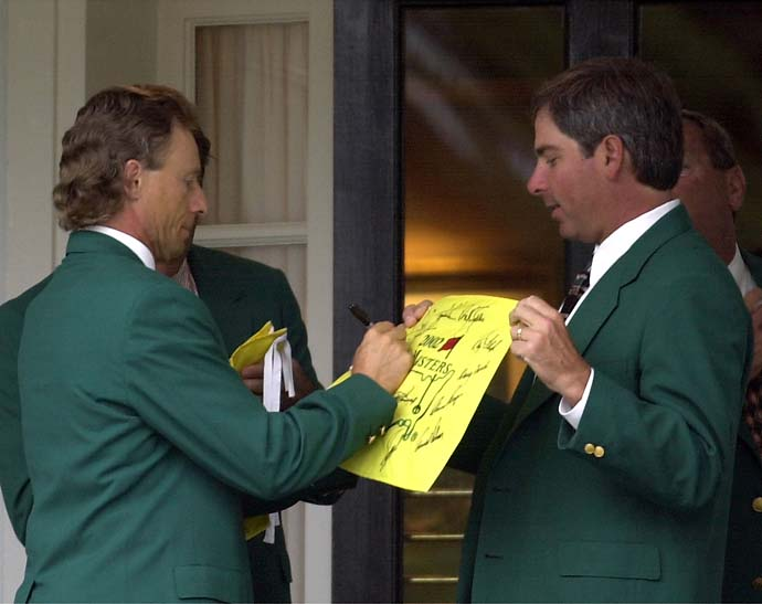 Two-time Masters Champion Bernhard Langer  signs an autograph for fellow former champion Fred Couples at the Augusta National Golf Club prior to the annual Champions dinner at the 2002 Masters.