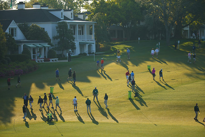 Fans cross fairway on 1st hole at Augusta National on Friday.