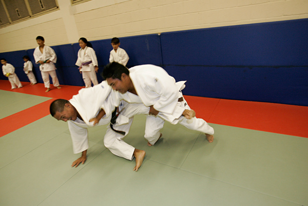 "Fujikawa, right, practiced judo with his father. Tadd won his first junior judo national championship at age eight. ""In judo he was like a wild animal,"" said Derrick, an instructor at the Salt Lake Judo Club. ""All the kids were a head taller, but they would cry when they had to face him because they were so scared."""