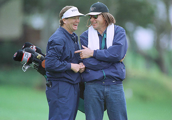 Nick Faldo sported a wig and shared a laugh with Peter Jacobsen while the pros caddied for their amateur partners at the 1996 Celebrity Shootout.