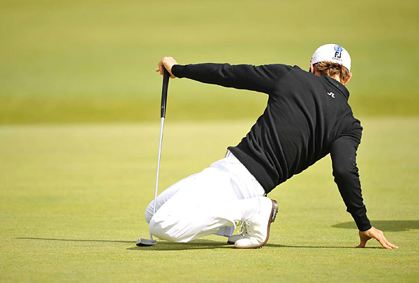 had a hard time getting into his signature putting stance as the wind wreaked havoc on players all afternoon.