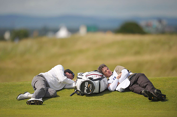 and his caddie Ted Scott took their break on the course while play was delayed due to high winds.