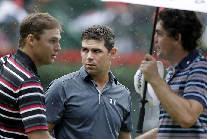 Nick Watney, Gary Woodland and Keegan Bradley, shake hands after finishing on the 18th hole of the Tour Championship on Saturday.
