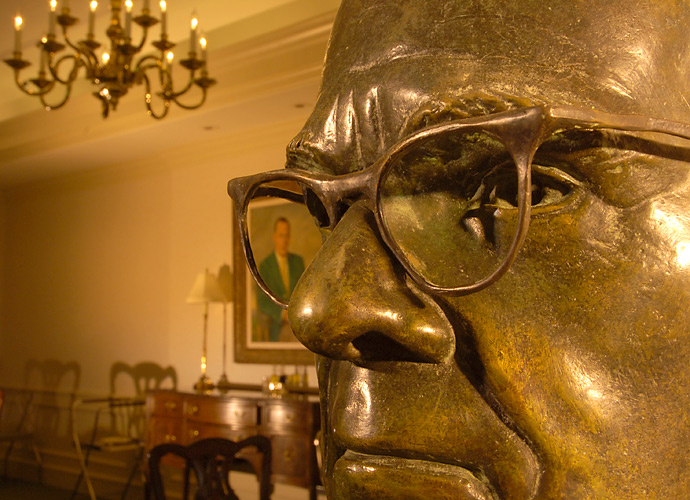 A bust of Augusta National co-founder Clifford Roberts sits in the foreground with a portrait of Bobby Jones hanging behind him