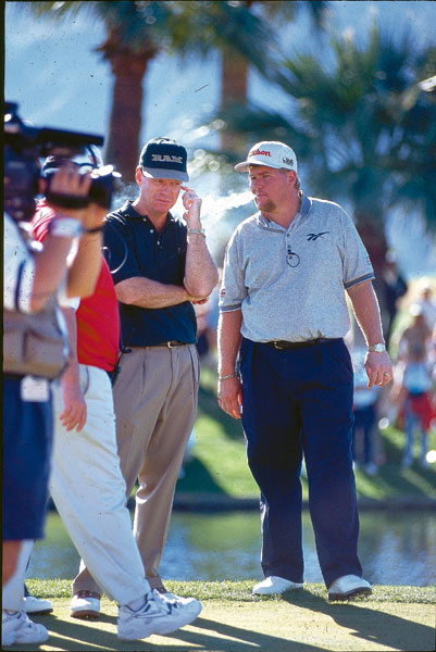 Perhaps the patron saint of all smokers on Tour, John Daly blows some smoke in an unamused Tom Watson's direction during the 1998 Skins Game in California.