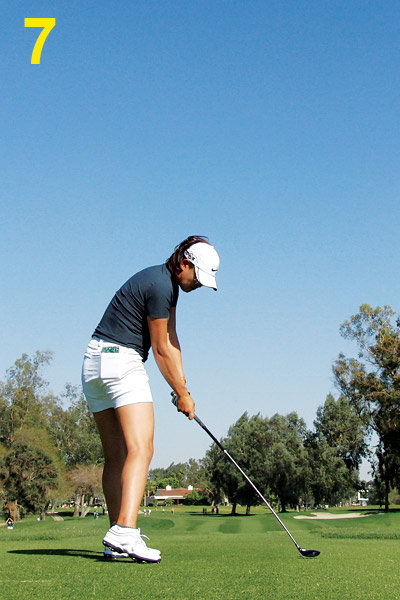 7. At impact Michelle's spine is slightly lower than at address and her left leg is starting to straighten. Staying down like this and rotating helps the club compress the ball as much as possible.