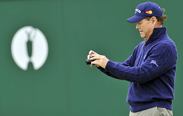 Tom Watson stopped on the 18th green to snap a picture. Watson won five Open titles in his career, and he nearly won a sixth in 2009 but lost in a playoff to Stewart Cink.