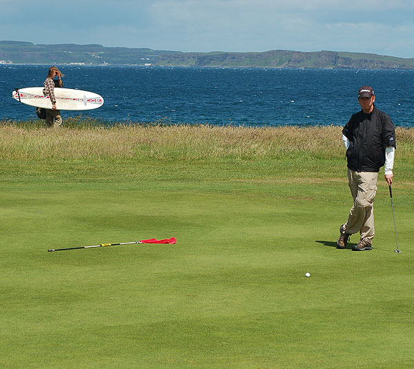A surfer looks on as Coyne waits to putt on a green at Ballycastle.