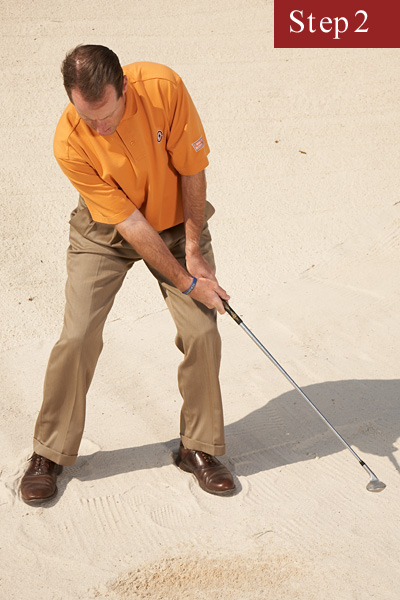 STEP 2                                              Aim for a spot an inch behind the ball, and as you enter the sand, keep your weight back and allow the club to pass your hands. It should feel like you're slapping the bottom of the club against the sand under the ball.