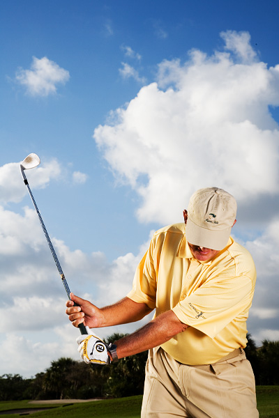 FEEL THE HINGE As you take the club back, notice how the split grip causes your wrists to hinge quickly and fully, with your left hand pushing out on the handle. Hinging your wrists like this allows you to hit down into the sand so that the club can pass under the ball.