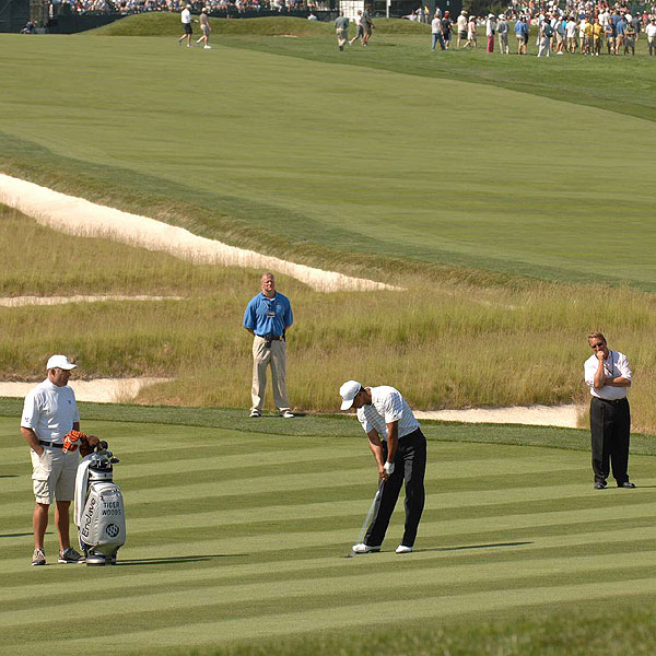 Tiger Woods takes a shot next to the Church Pews during a practice round.