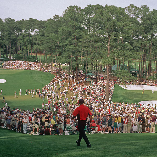 Tiger walks toward the fairway as thousands of fans look on during his first Masters appearance in 1997.