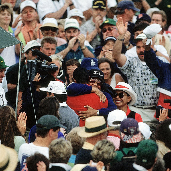 Tiger hugs his father, Earl, after Sunday play as fans and media watch at Augusta National.