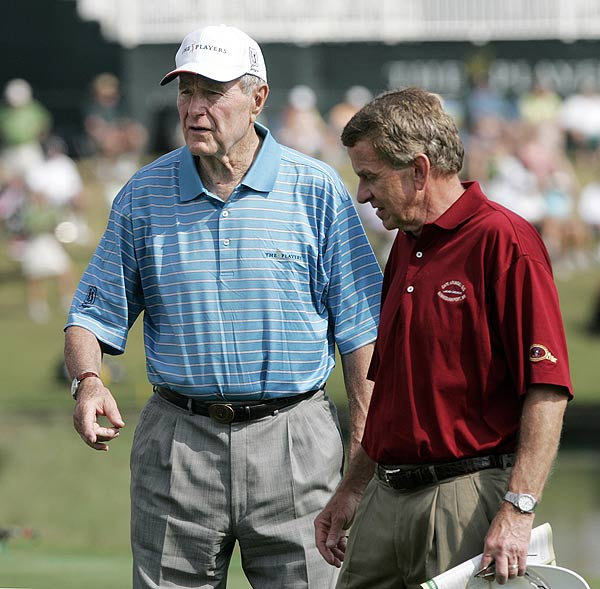 Former President George Bush watched players on No. 17 on Friday with Tim Finchem.