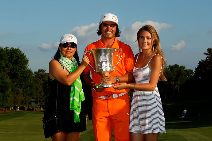 Rickie Fowler celebrates with the championship trophy alongside his mother, Lynne Fowler, and girlfriend Alexandra Brown after defeating Rory McIlroy and D.A. Points in a playoff during the final round to win the Wells Fargo Championship at the Quail Hollow Club on May 6, 2012, in Charlotte, N.C..