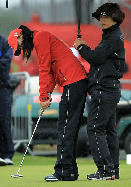 Michelle Wie practices her putting as her mother, Bo Wie, holds an umbrella during the second round of the 2010 Ricoh Women's British Open at Royal Birkdale.
