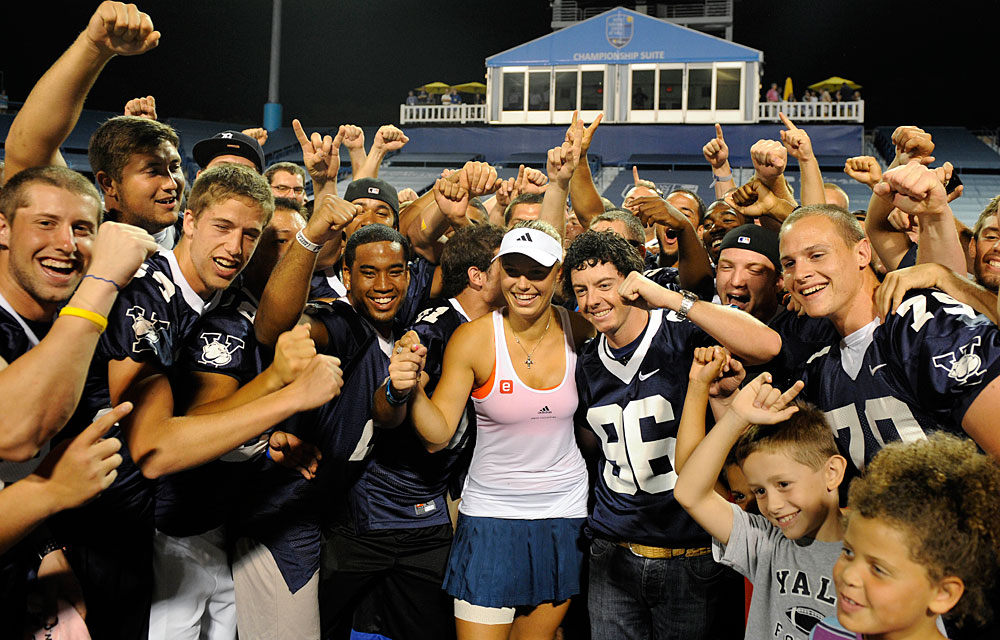 Aug. 26, 2011: Wozniacki and McIlroy celebrated with the Yale football team after her 7-6, 6-3 semifinal victory over Francesca Schiavone at the New Haven Open.