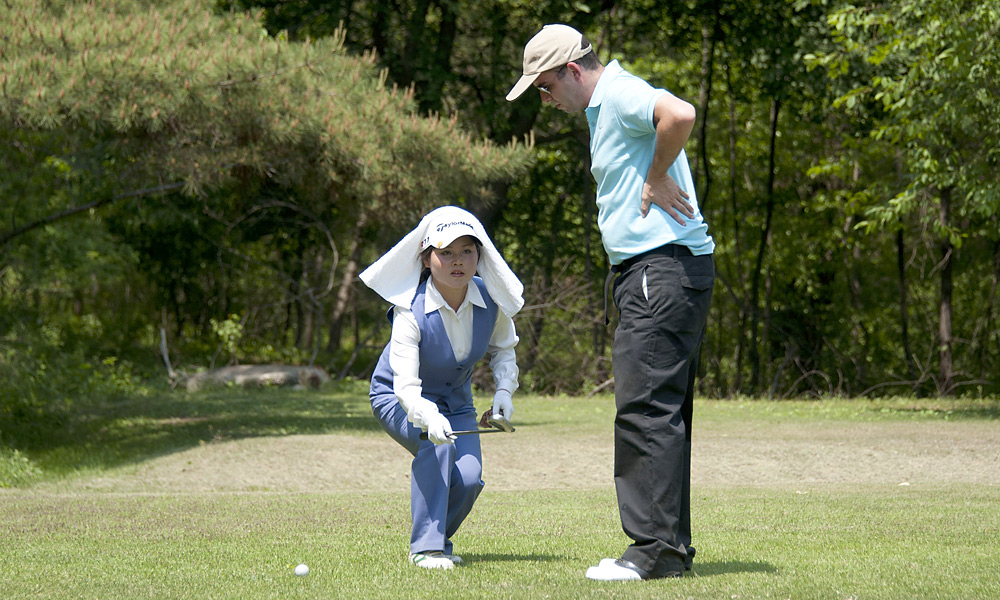 STRAIGHT TALK: A Pyongyang Golf Course caddie helps a contestant with his alignment.