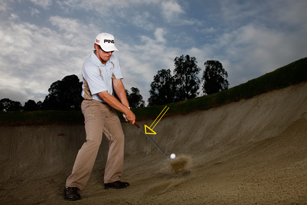 My Pressure Bunker-Save Key                                              Place the ball forward in your stance so you can come through nice and shallow. I like to stay centered with my chest — I don't want to move laterally or forward. Keep the club real low though the sand — don't pick it up or stab it into the ground. Trust your wedge, and trust that the ball will spin. It will. Don't make this shot harder than it needs to be.