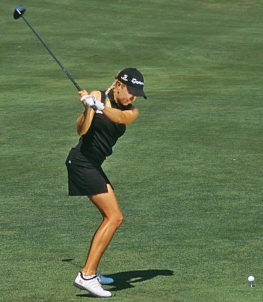 "Like all good players, Natalie instinctively understands that the quickest way to lose power is to release the club early — that is, to lose the 90-degree angle between your left forearm and the shaft. In the photo above, Natalie maintains a solid ""L"" position with her left arm and the clubshaft as she begins her downswing — her wrists stay set, which creates a solid delivery position for the club and a ton of distance-producing leverage."