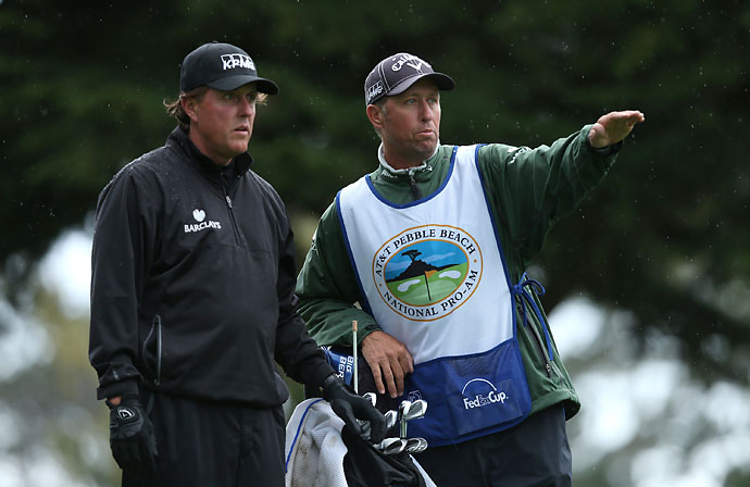Phil Mickelson and his caddie Bones MacKay discuss an approach shot on the tenth hole fairway during the third round of the AT&T Pebble Beach National Pro-Am at the Spyglass Hill Golf Course on Saturday.