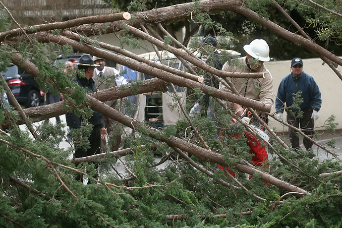Workers clear away a tree that fell in the wind at the Lodge at Pebble Beach near the 18th green during the third round of the AT&T Pebble Beach National Pro-Am on Saturday.