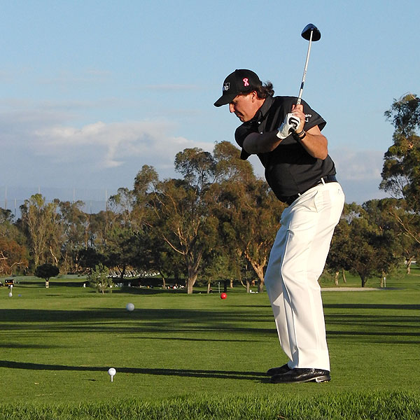 As he starts his downswing, his arms are in front of his body. Notice how the arms and body are connected.