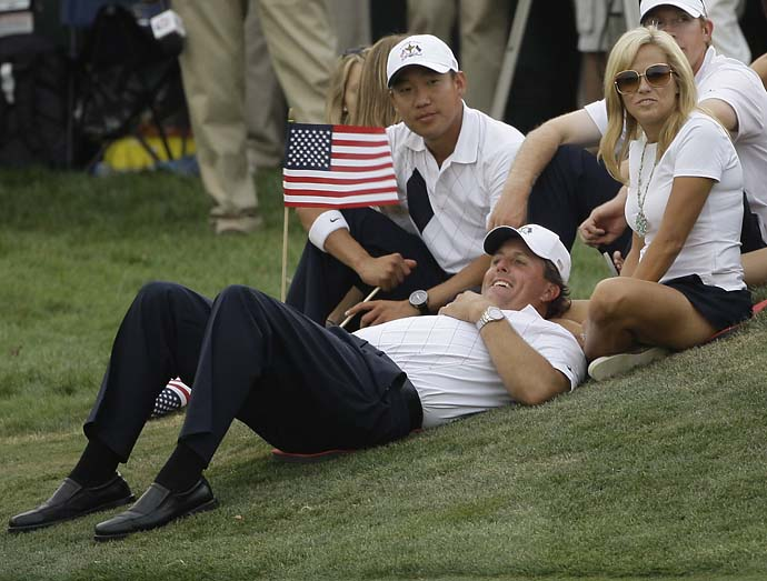 Phil Mickelson lies in front of his wife Amy and teammate Anthony Kim on the 17th green during the four-ball matches at the 2008 Ryder Cup golf tournament at the Valhalla Golf Club, in Louisville, Ky.