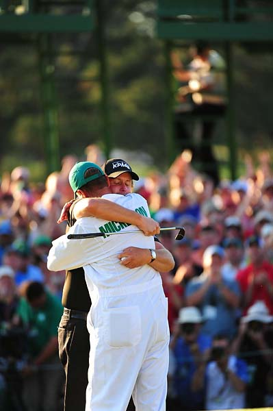 Phil Mickelson hugs caddie Bones Mackay after winning the 2010 Masters.
