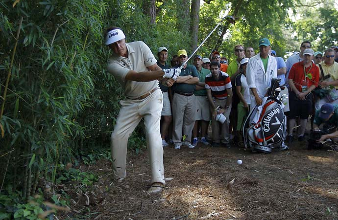 Phil Mickelson hits his shot right-handed out of the bamboo trees on the fourth hole during final round play in the 2012 Masters Golf Tournament at the Augusta National Golf Club in Augusta, Georgia, April 8, 2012. Mickelson made a triple-bogey six on the hole, effectively taking him out of contention and Bubba Watson won the Masters.